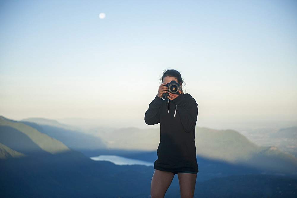 Mid adult woman photographing with mountains in background