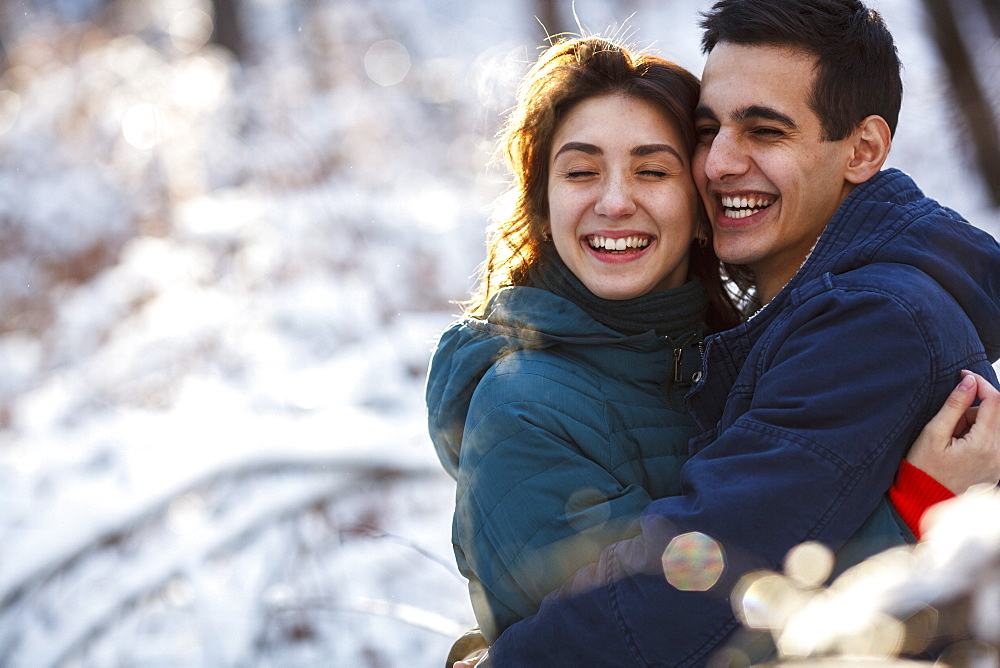 Cheerful young couple embracing on field during winter