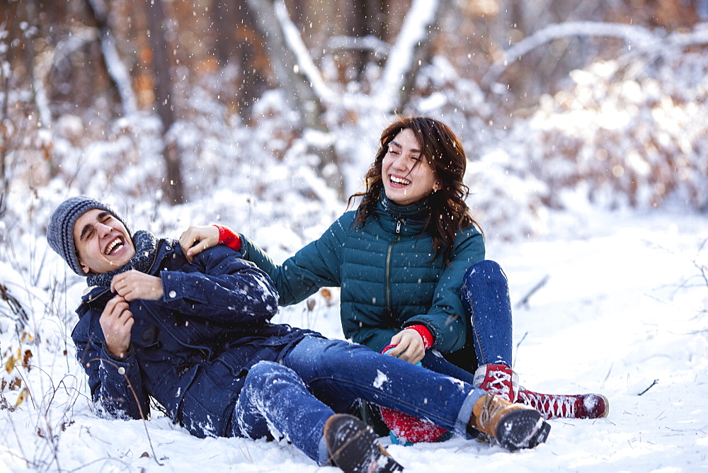 Full length of playful young couple sitting on snowy field