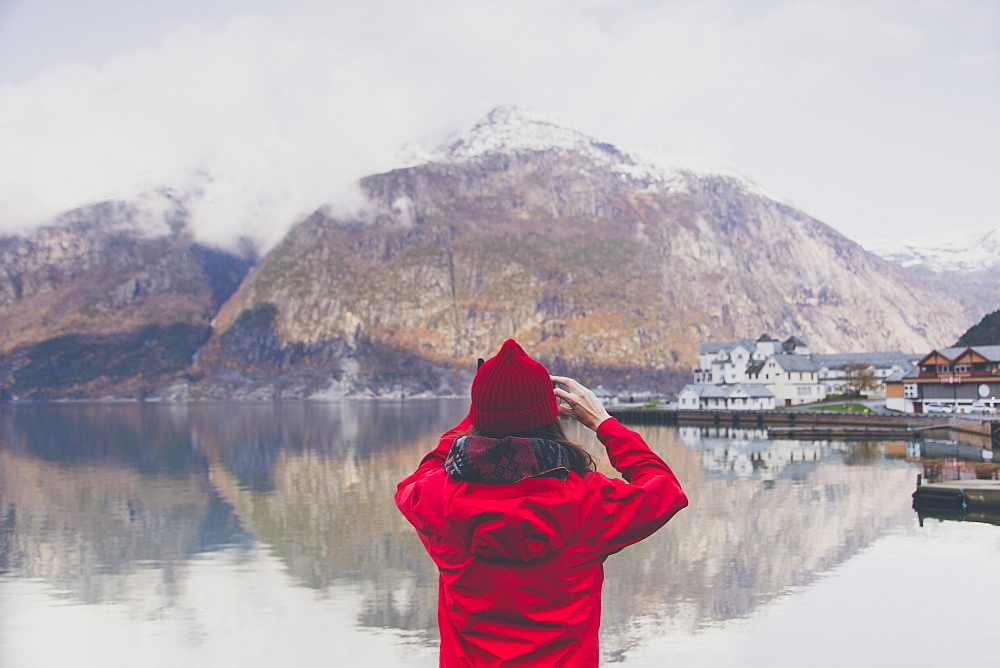 Rear view of woman photographing mountains