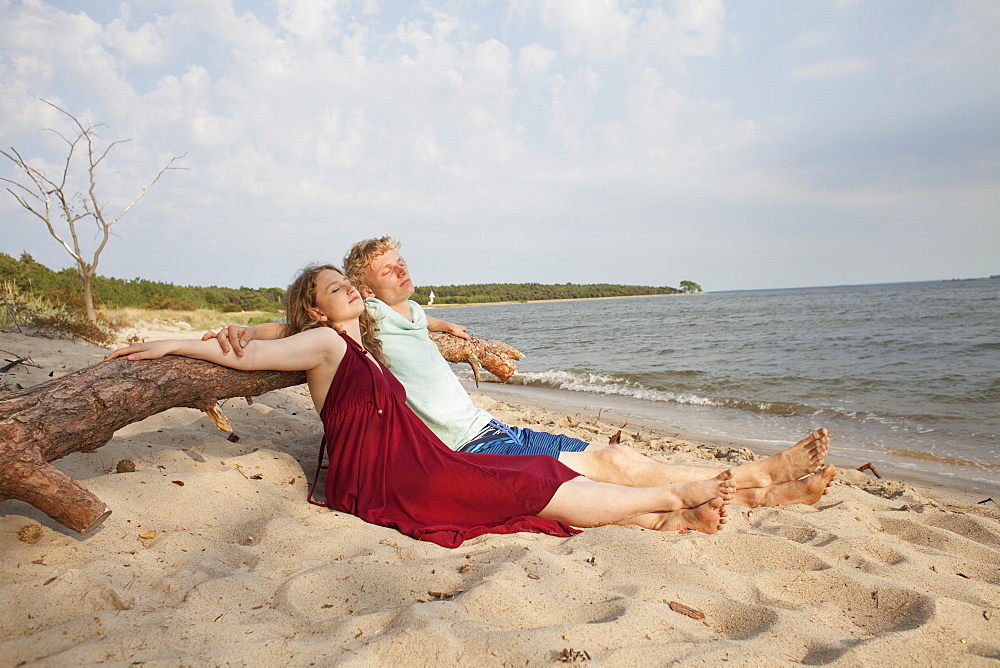 Friends relaxing while leaning on driftwood at beach against sky