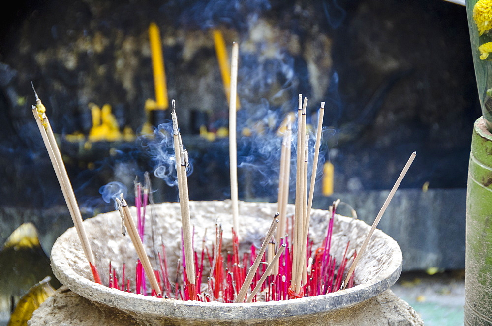 Smoke emitting from incense sticks in container at temple