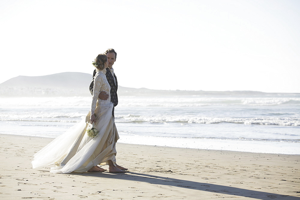Full length of loving bride and groom walking at beach
