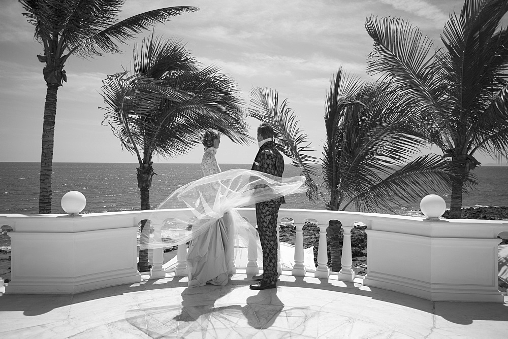Full length of bride and groom standing on building terrace while looking at sea