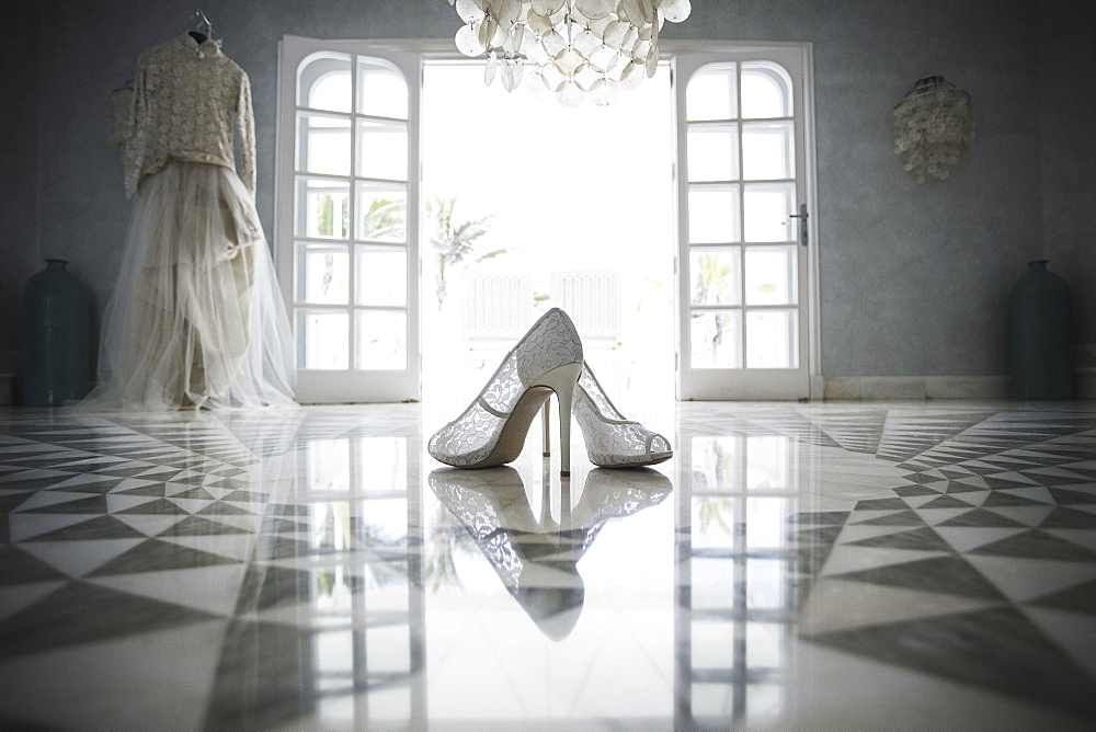 High heels and wedding dress in front of open door