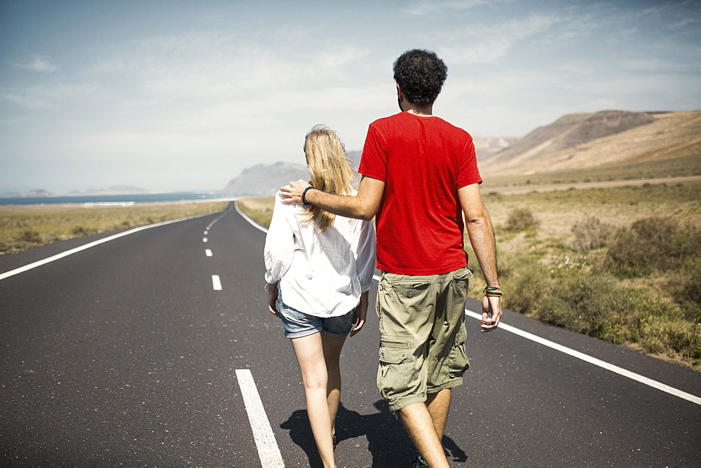 Rear view of couple with arm around walking on road