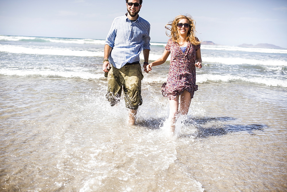 Cheerful couple running in sea on sunny day