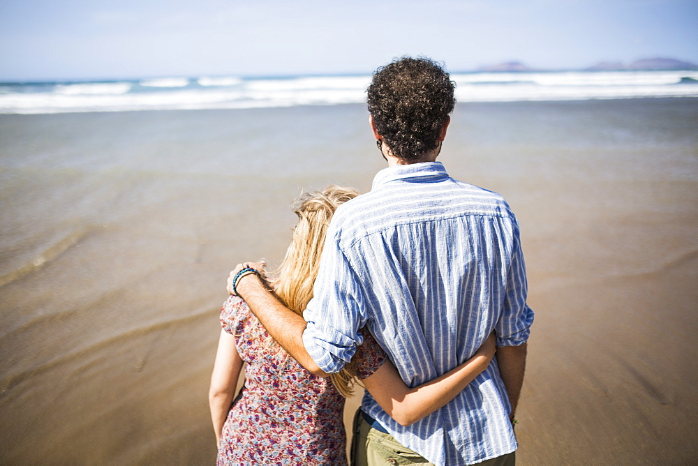 Rear view of loving couple standing arm around at beach