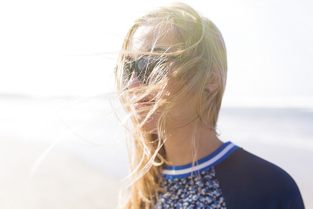 Happy young woman with windswept hair at beach