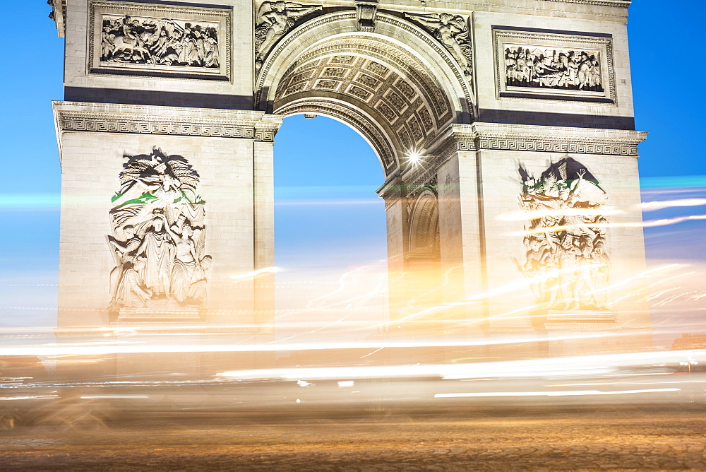 Illuminated light trails against Arc de Triomphe
