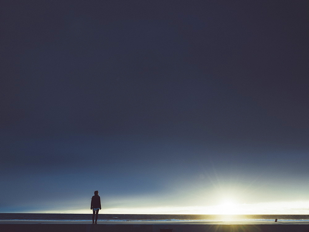 Woman standing on seashore against cloudy sky during sunny day