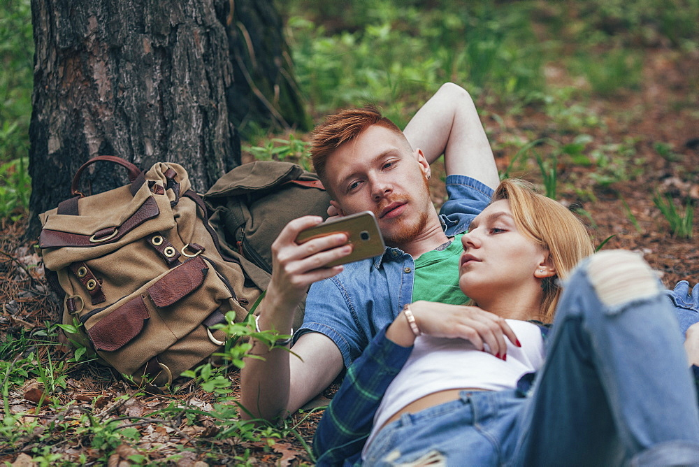Young couple looking in smart phone while lying by tree at forest