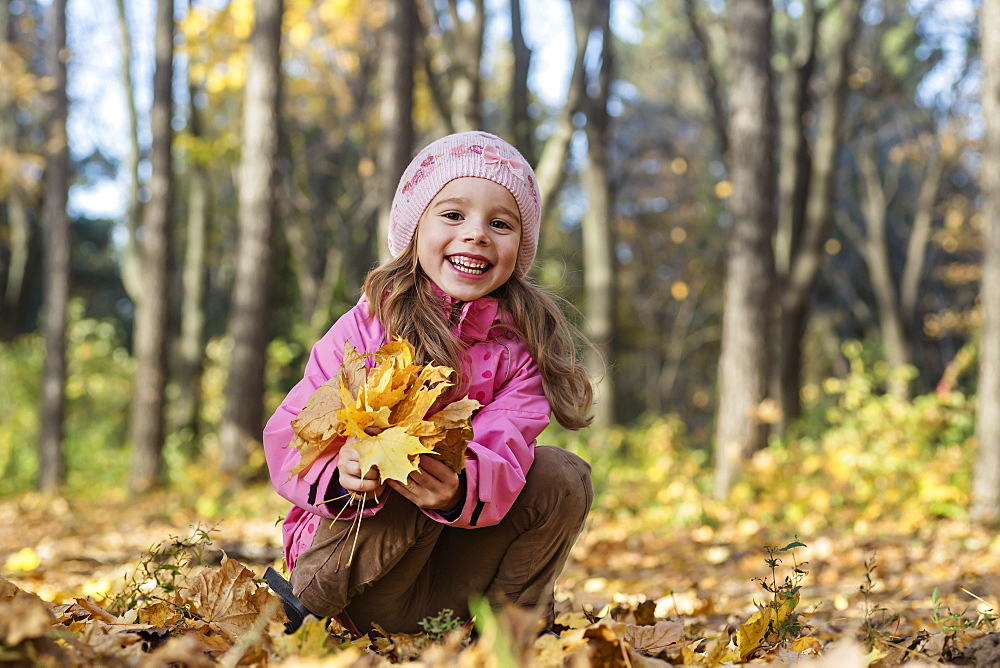 A cheerful girl picking up autumn leaves in a wooded area