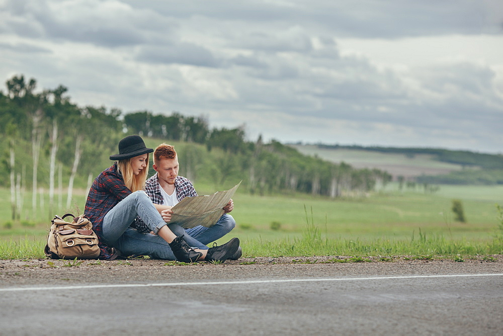 Couple reading map while sitting on roadside against sky