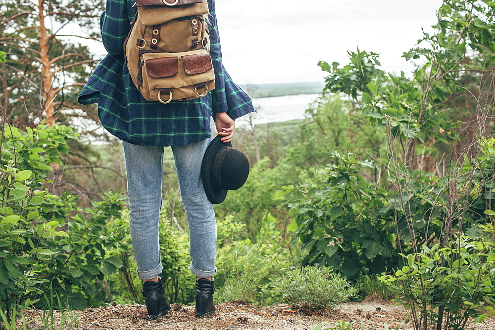 Low section of female backpacker holding hat while standing at forest