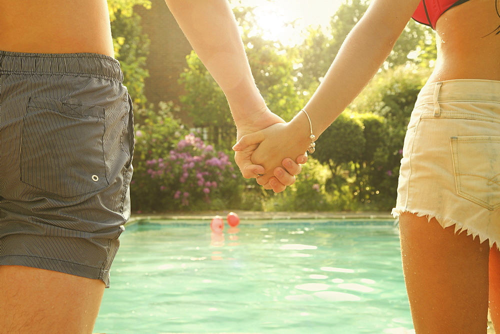 Rear view midsection of young man and woman holding hands while standing by swimming pool