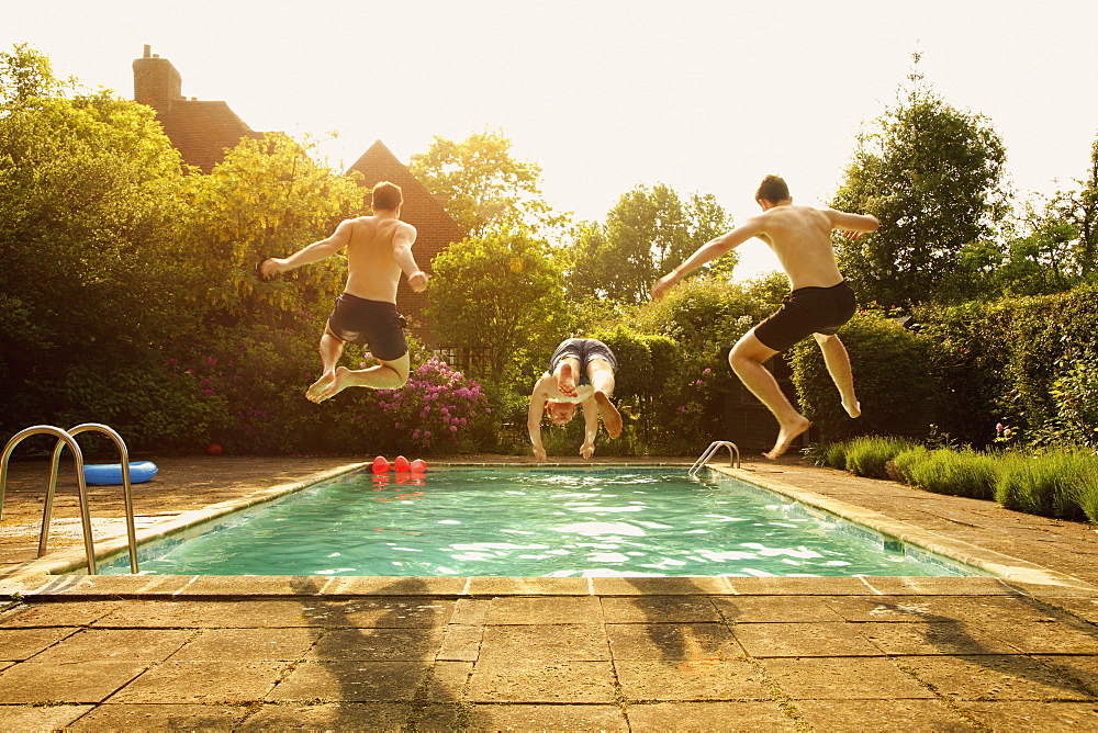 Rear view of men jumping in swimming pool during summer