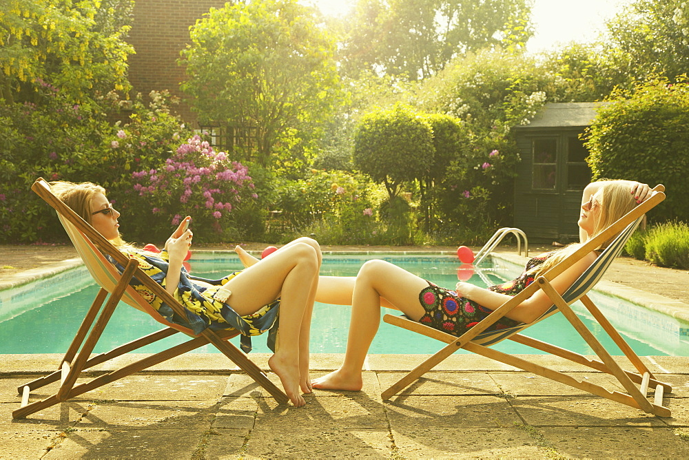 Side view of female friends relaxing on deck chairs at poolside during summer