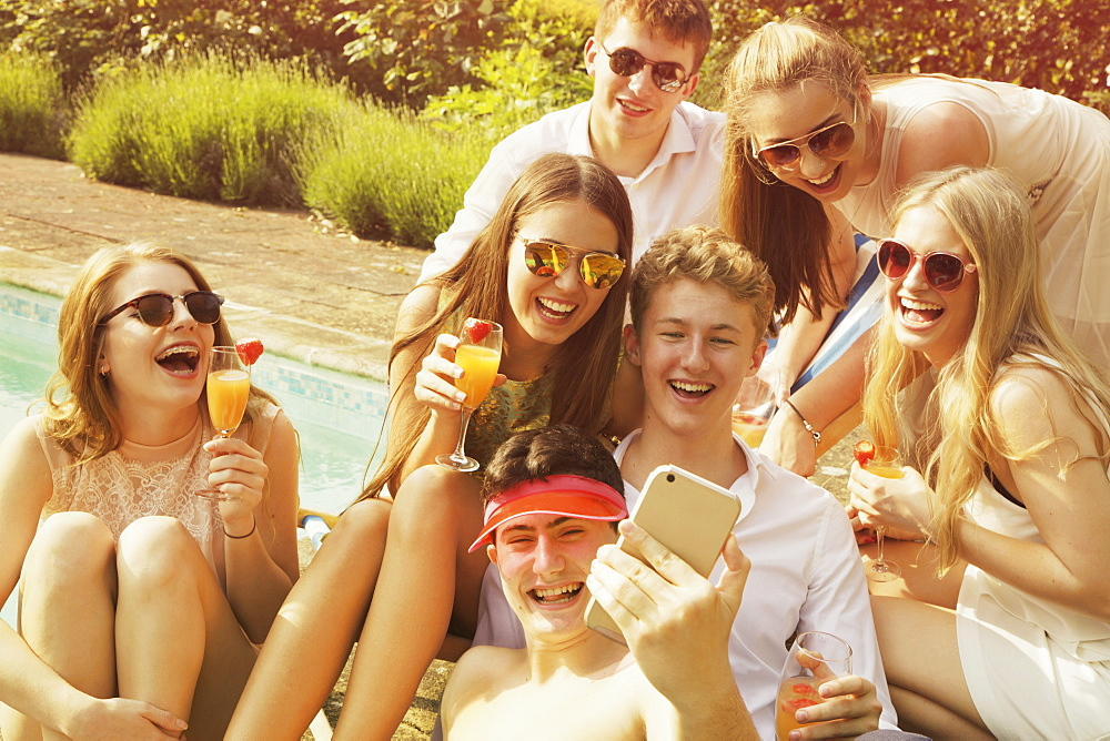 Cheerful friends taking selfie while relaxing by poolside on sunny day