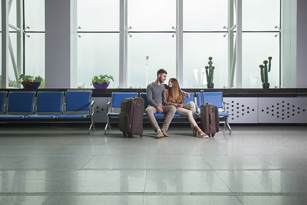 Young couple with luggage sitting on chairs at airport
