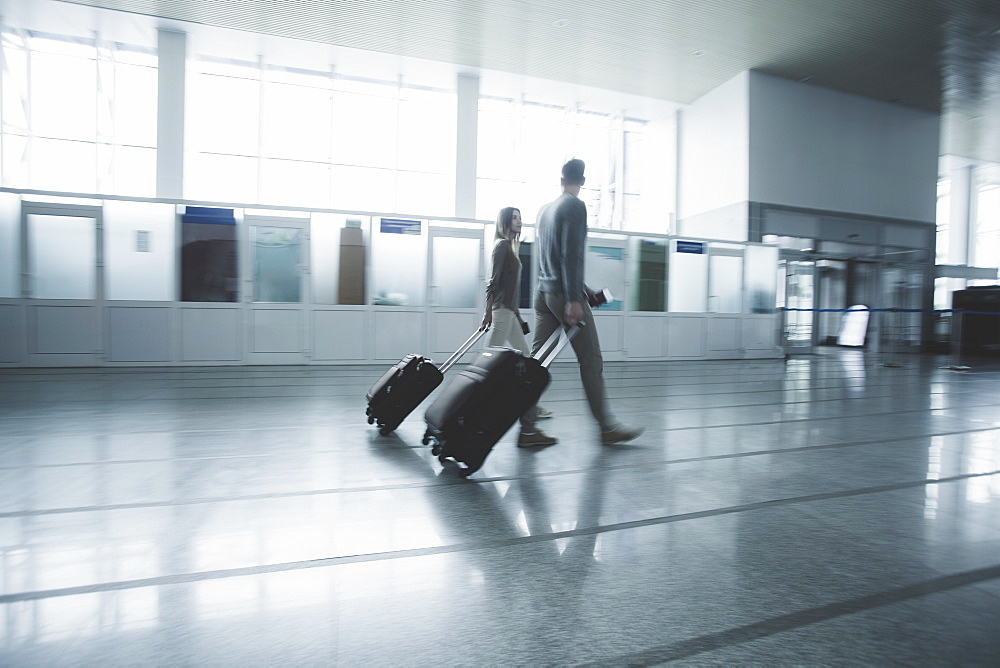 Young couple with luggage walking at airport