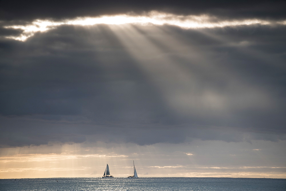 Distant view of yachts in sea against dramatic sky