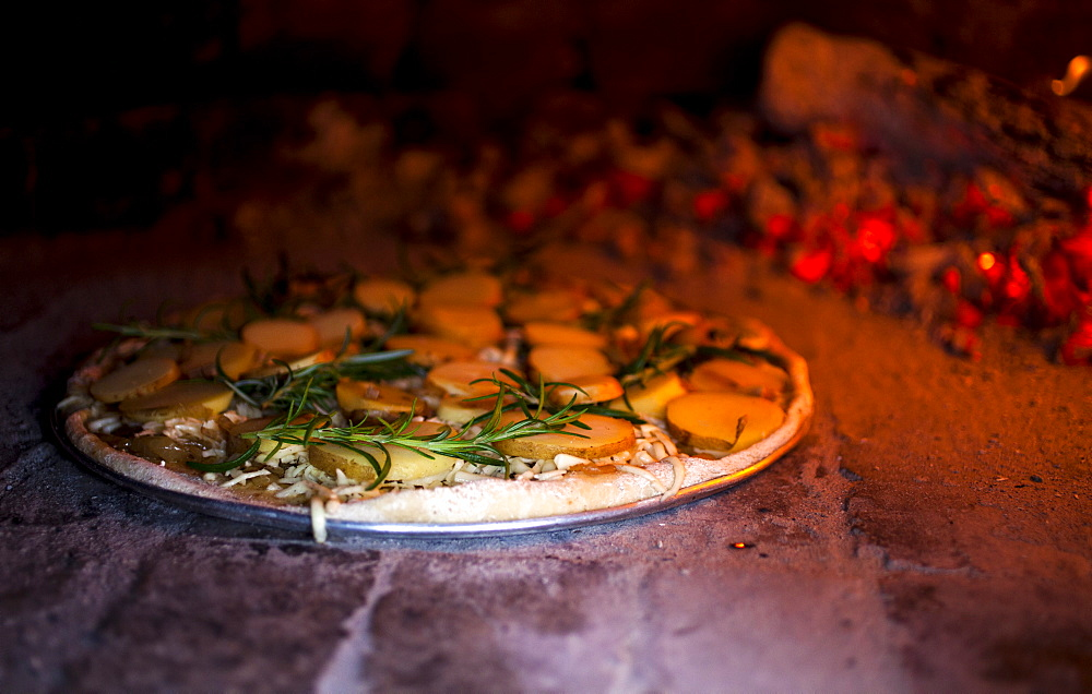 A rosemary and potato pizza baking in a brick pizza oven