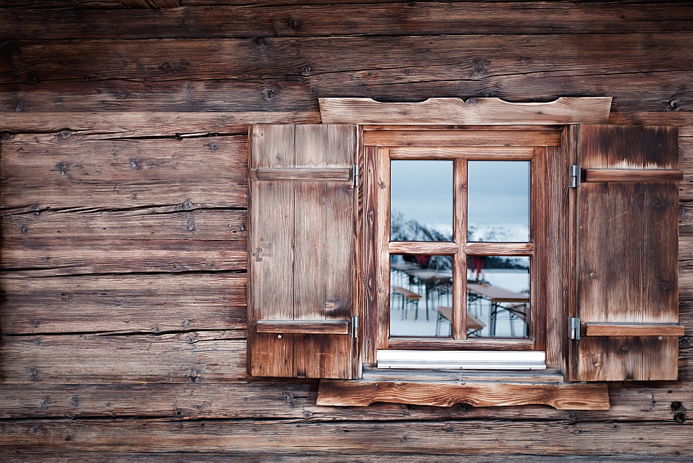 Reflection on glass window of log cabin, Kufstein, Tyrol, Austria