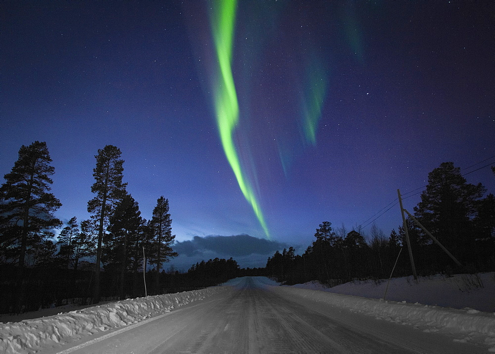 Scenic view of Aurora Borealis over snow covered road amidst silhouette trees at night