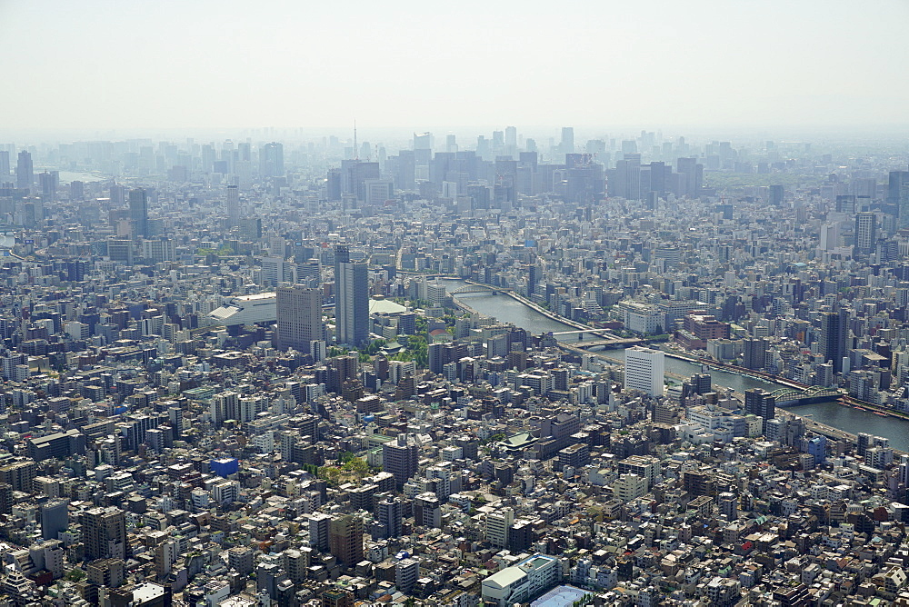 Aerial view of crowded cityscape against sky on sunny day, Tokyo, Japan