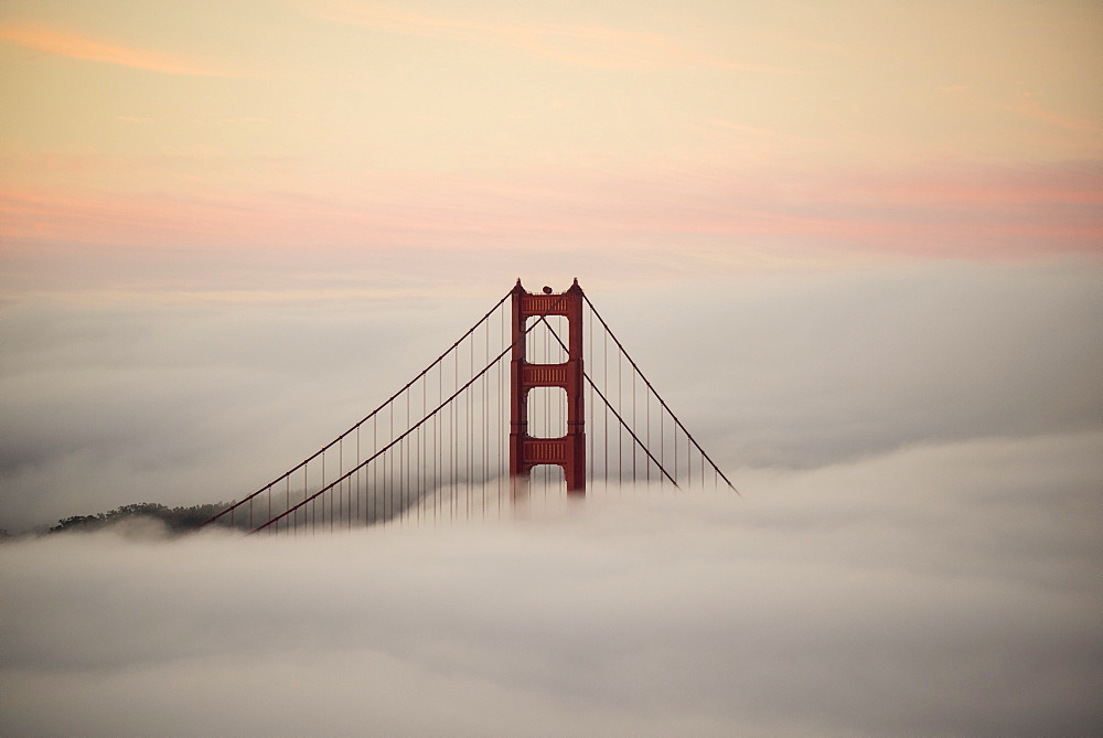 Golden Gate Bridge surrounded by fog during sunset, San Francisco, California, USA