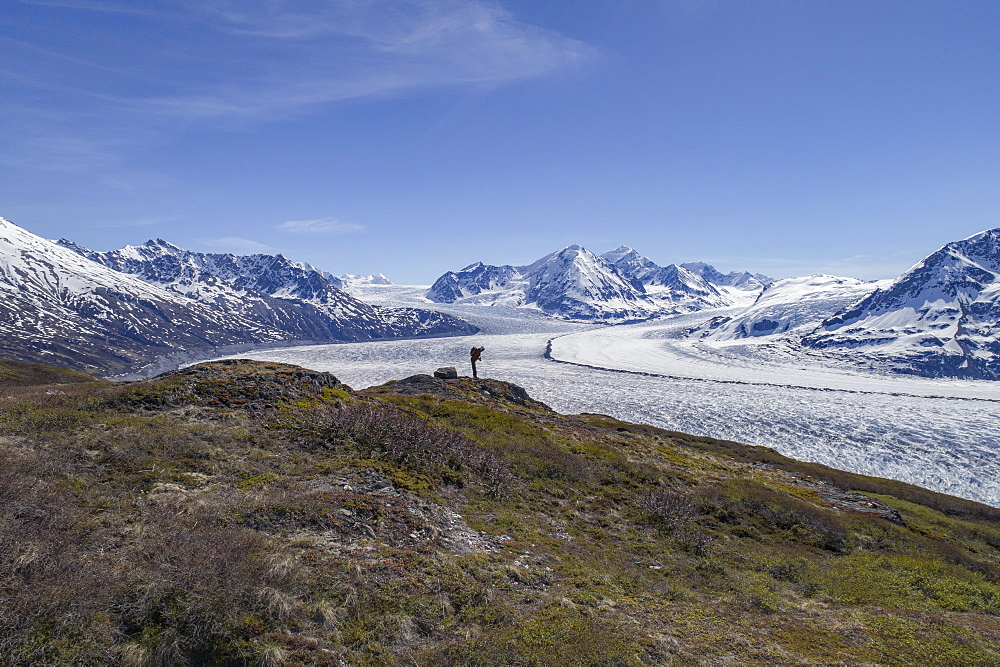 Full length of hiker looking at glacier against blue sky, Knik Glacier, Palmer, Alaska