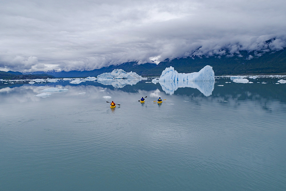 People canoeing in glacier lagoon against cloudy sky, Knik Glacier, Palmer, Alaska, USA