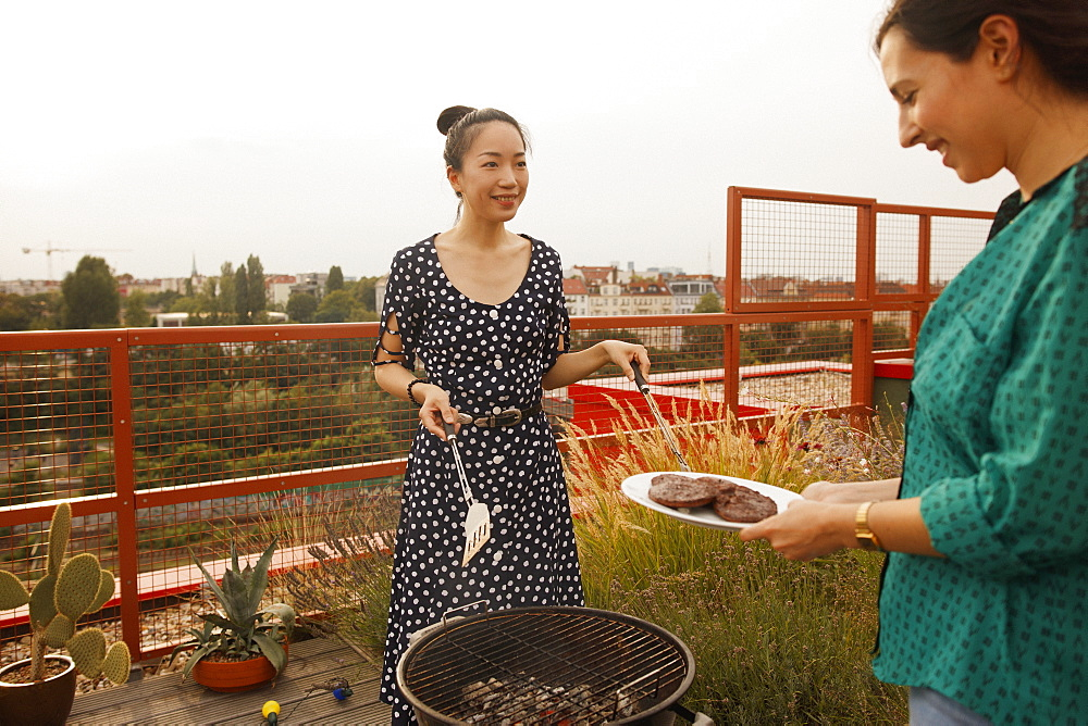 Smiling woman serving freshly grilled steak to female friend on patio