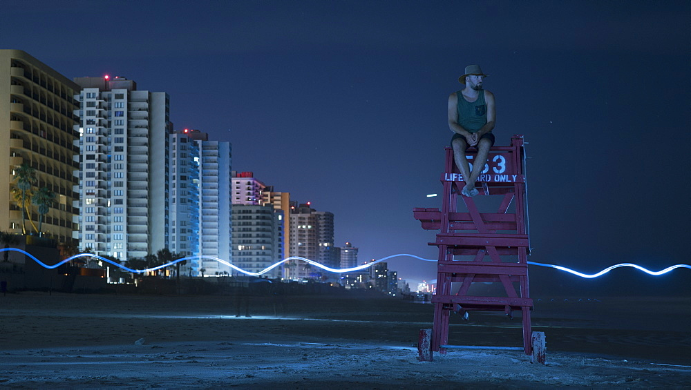 Man sitting on lifeguard chair against sky at night, Daytona, Florida, USA - 1177-1890