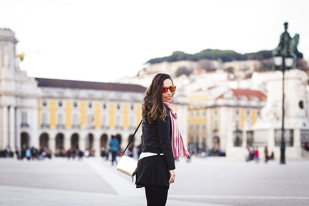 Smiling mid adult woman standing at town square against building in city, Lisbon, Portugal - 1177-1893