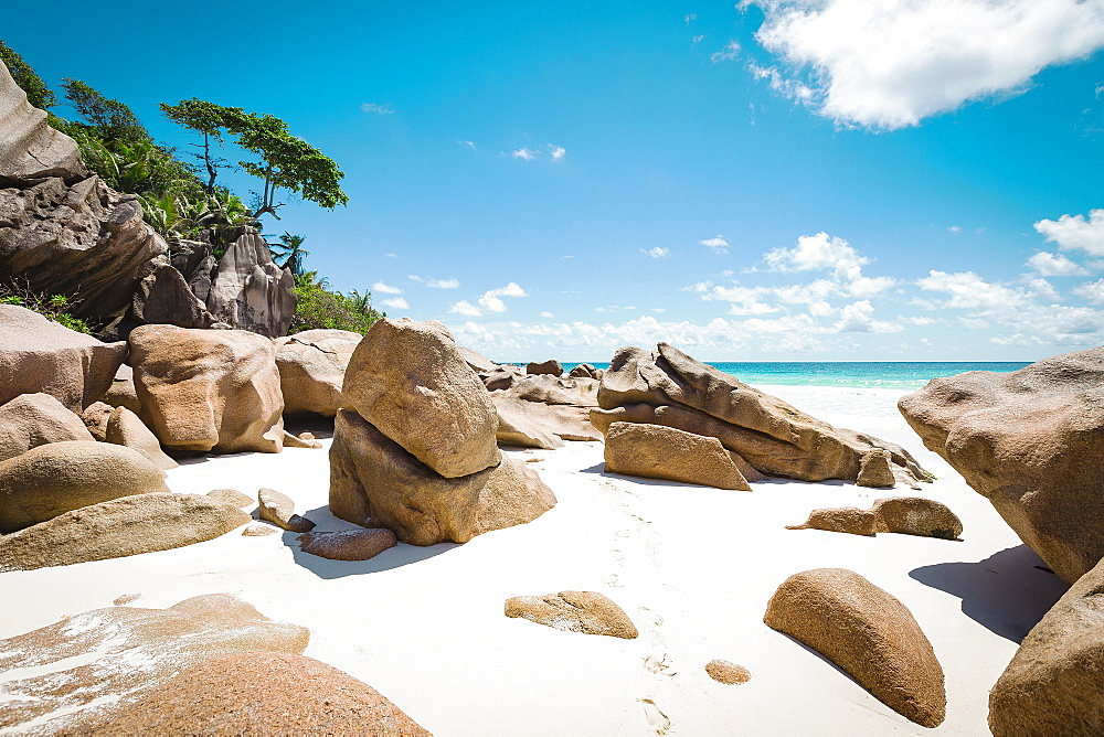 Rocks at beach against blue sky during sunny day, Island of La Digue, Seychelles