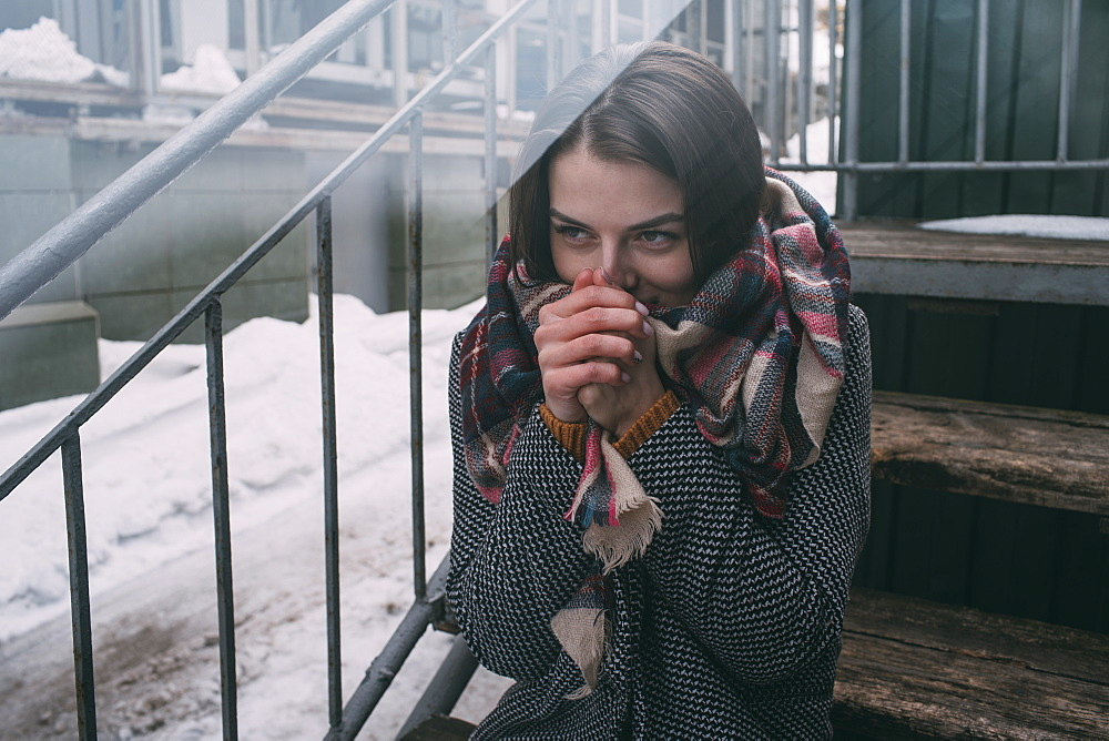 Young woman warming hands on cold, winter stoop