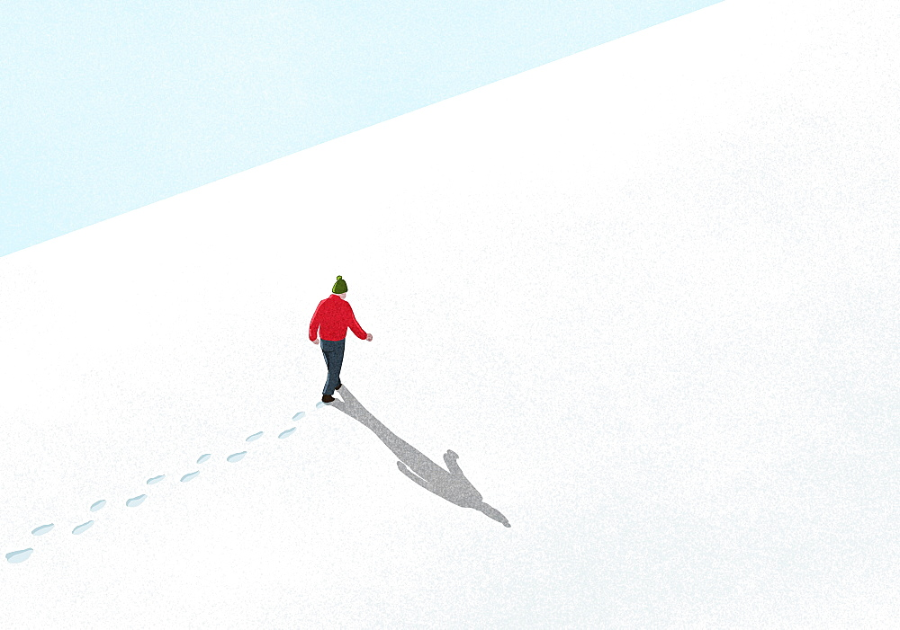Man walking up snowy slope