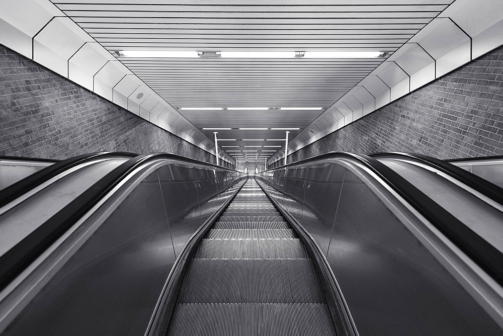 Black and white of descending escalator
