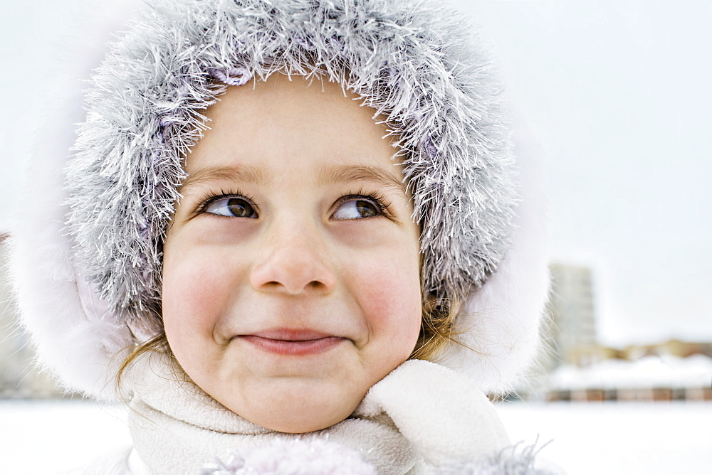A mischievously smiling young girl wearing a fur hat outdoors in winter