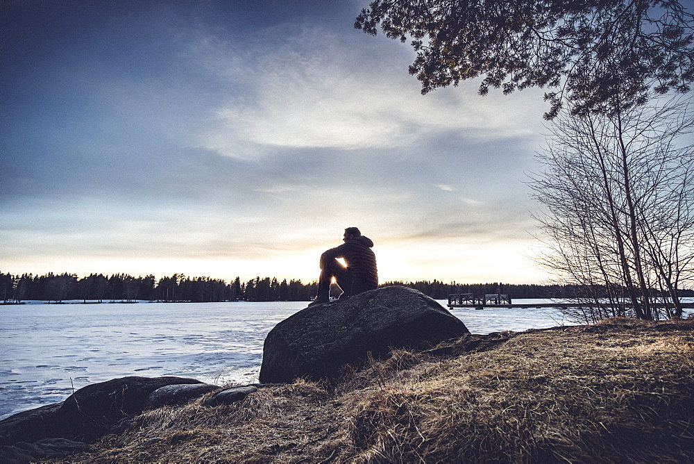 Man sitting on rock overlooking Lake Nydala, Umea, Sweden