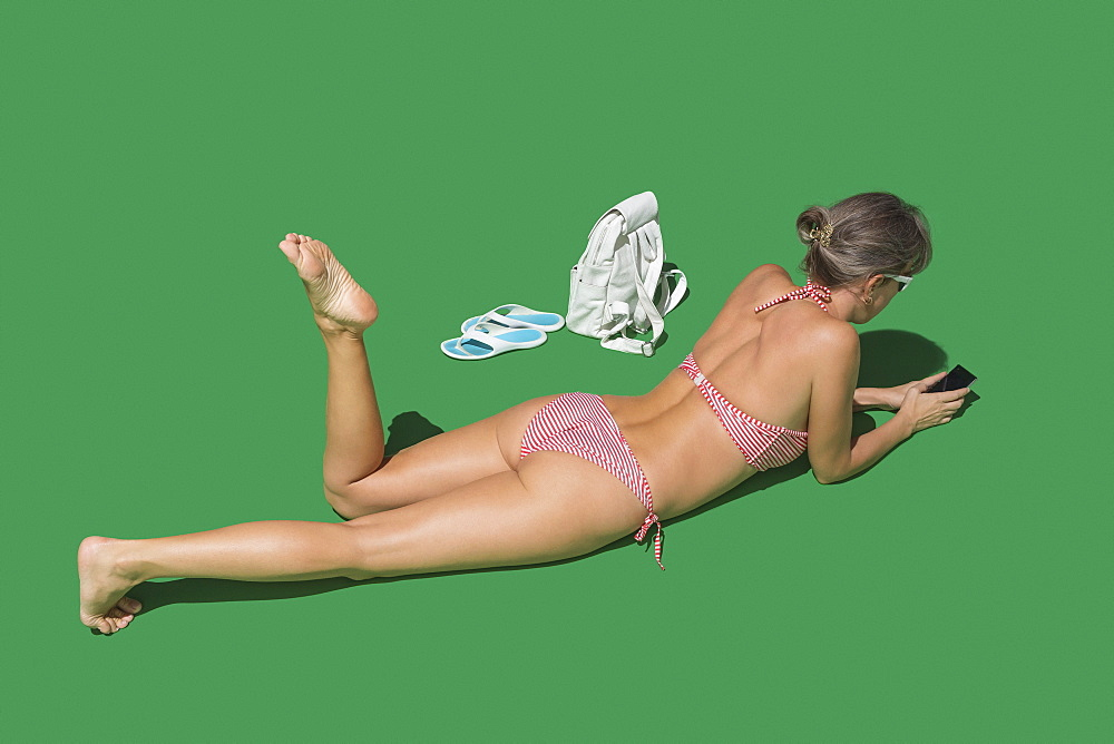 Woman in bikini sunbathing on green background