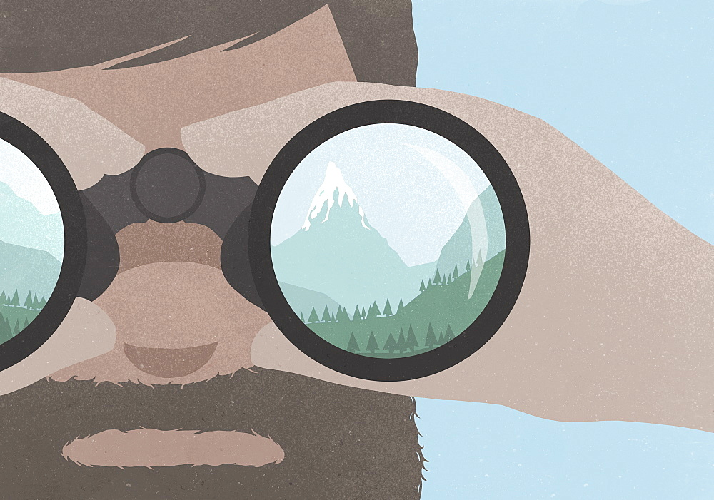 Reflection of a mountains in binoculars held by a man with a beard