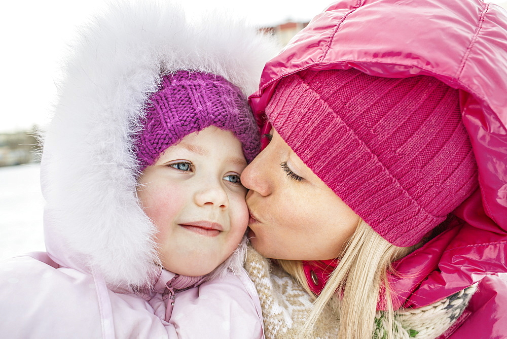 A mother kissing her daughter outdoors in winter