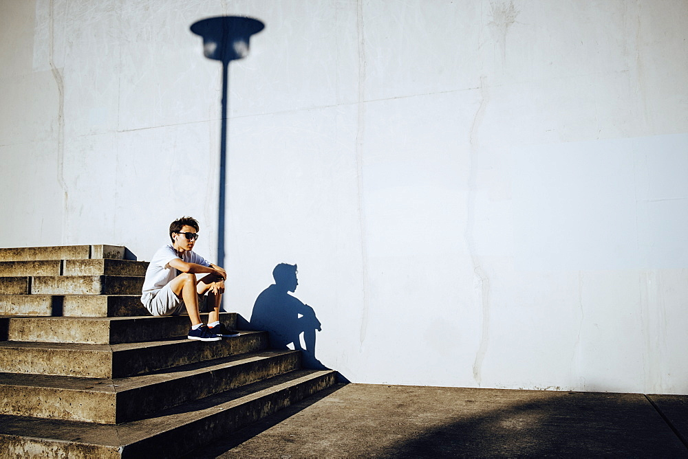 Young male runner resting on sunny urban steps