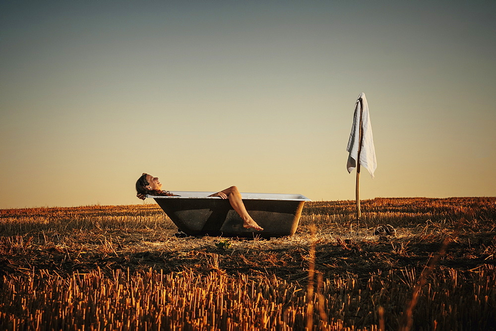 Woman relaxing in bathtub in rural field