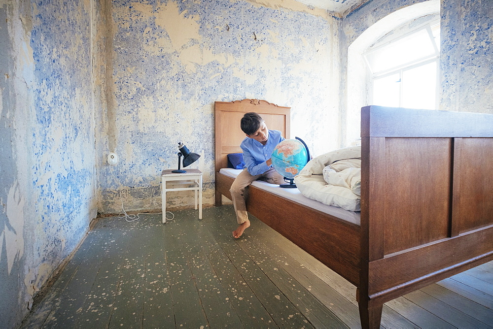 Boy looking at globe on rustic farmhouse bed