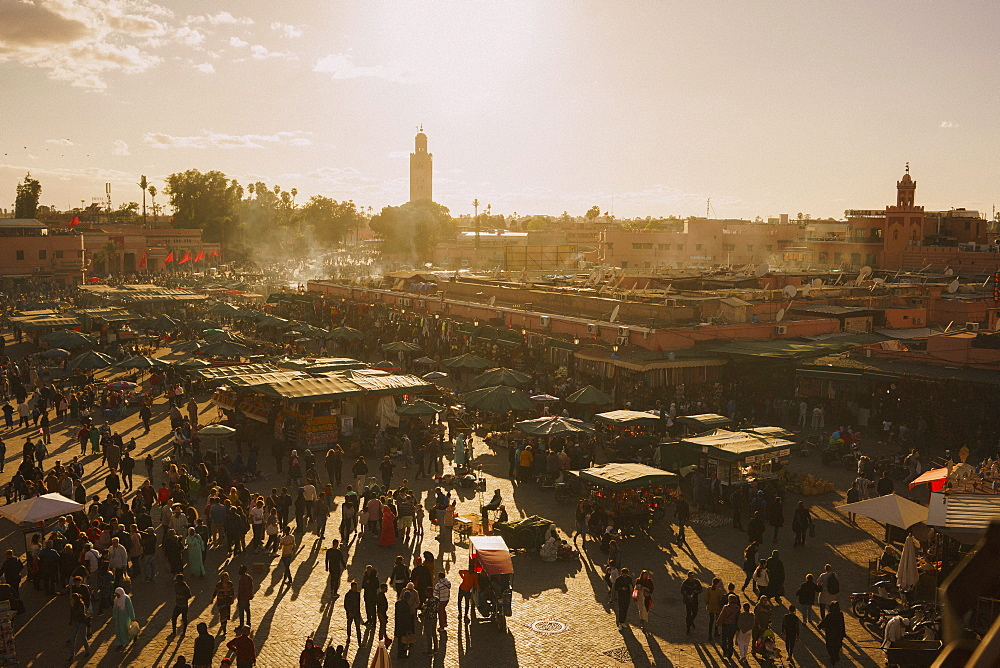 View of sunny, bustling souk market in Djemaa El Fna Square, Marrakesh, Morocco