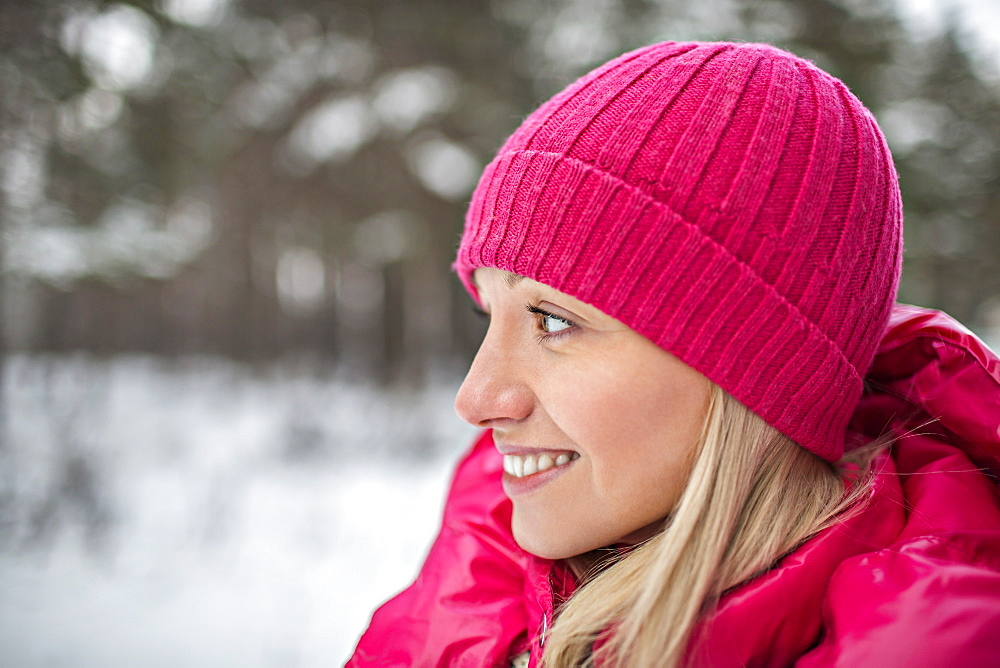 A woman wearing bright pink winter clothing outdoors